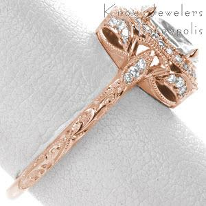 Rose gold engagement ring in Dayton with diamond halo, oval center stone and relief engraving.