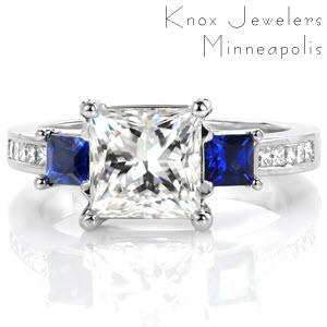 Design 3271 takes a modern look with graduating elevations and regal color accents. The center 1.50 carat princess cut diamond is flanked by two deep blue square cut blue sapphires. Continuing an elevation step, the band is dressed with channel set princess cut diamonds and woven trellis prongs.