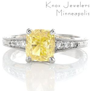 The vivid 1.70 carat fancy yellow cushion cut diamond takes center stage in this vintage inspired ring. Yellow gold filigree curls compliment the warm hue of the center stone. Ornate patterns are engraved on three faces of the ring for an antique finish. The edges are detailed with milgrain texture.