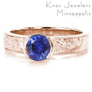 Rose gold custom engagement ring in McAllen with scroll hand engraving and a round blue sapphire center stone.