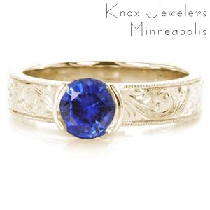 Antique inspired custom engagement ring in Vancouver with scroll hand engraving and a round blue sapphire center stone.