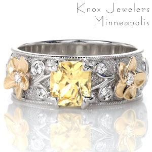 Unique sapphire engagement ring in Denver. Custom floral yellow sapphire engagement ring features plumeria flowers in yellow gold on a platinum band with custom petal prongs for the center sapphire. Diamonds adorn the plumeria flowers and filigree on the band.