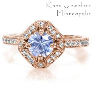Custom antique inspired engagement ring featuring a round light blue sapphire held in a unique halo setting.