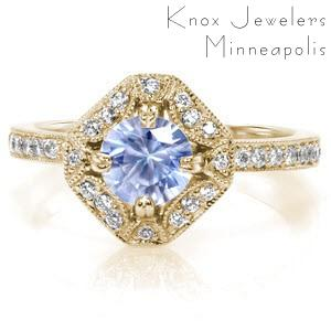 Custom antique inspired engagement ring in Hartford featuring a round light blue sapphire held in a unique halo setting.