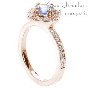 Custom antique inspired rose gold engagement ring in Sioux Falls featuring a round light blue sapphire held in a unique halo setting.
