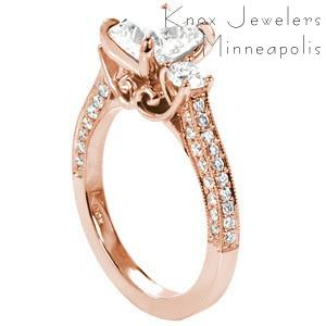 Custom rose gold three stone engagement ring with a cushion cut diamond center surrounded by beads set diamond and a floral profile design in Des Moines.