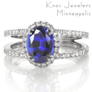 A grand 1.50 carat oval cut blue sapphire creates a beautiful statement of sophistication for Design 3308. Crafted in 14k white gold, hand formed U-Cut prongs accentuate diamonds around the halo and band. A split shank flares towards the center stone and also tapers at the band bottom for a comfortable fit.