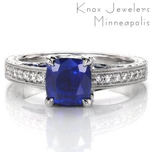 This elegant antique inspired design features a 1.00 carat cushion cut blue sapphire in four prongs. Hand engraving, diamonds and milgrain detail the sides of the ring for a vintage appeal. Marquise shaped petals are embellished with diamonds and open pockets are adorned with blue sapphires for a truly antique feel.