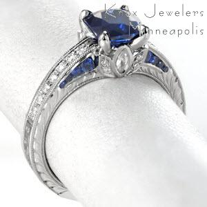 Antique sapphire engagement ring features diamond and sapphire side stones in Chicago. The stunning hand engraved patterns complete this hand crafted look.