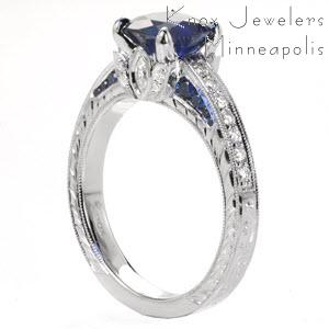 Redwing custom engagement ring with a cushion cut blue sapphire center stone atop a hand engraving and floral designed band.