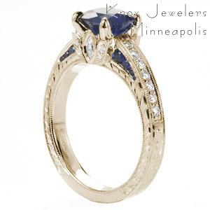 Stamford custom engagement ring with a cushion cut blue sapphire center stone atop a hand engraving and floral designed band.