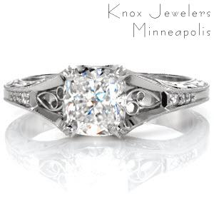 A 1.20 carat cushion cut center stone is fashioned in this vintage inspired design. Hand wrought filigree adds a decorative statement to the top and sides of the ring. The scroll pattern is highlighted by the contrast of the carefully stippled background. Accent diamonds adorn the band to add sparkle and brilliance.
