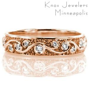 Custom rose gold wedding ring in Baltimore with a scroll pattern highlighted by bezel set diamonds.