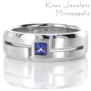 Modern lines and contrasting finishes highlight a natural blue sapphire in Design 3354. Crafted in 14k white gold, a square cut natural blue sapphire is outlined with bold open-cut grooves. The hand-applied brushed finish and high polish beveled edges bring balance to this wider band.