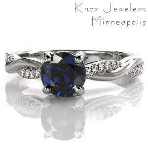 The stunning 1.00 carat blue sapphire enhances the cool tone of this white gold ring. A row of round brilliant diamonds are interwoven between a high polish band, for dimension and contrast. Accent diamonds adorn the basket setting for brilliance. The profile features open pockets for a stylish side view.