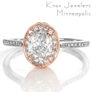 Design 3364 is a custom engagement ring modified from its original design into a two tone masterpiece. A 1.00 carat oval cut diamond is set into a rose gold central arrangement and surrounded by a flattering diamond halo. The contrasting white gold diamond band interlocks into this antique detailed setting.