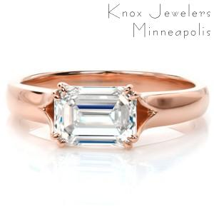 Custom solitaire rose gold engagement ring in Tampa with a unique horizontal set emerald cut center diamond held by double prongs.