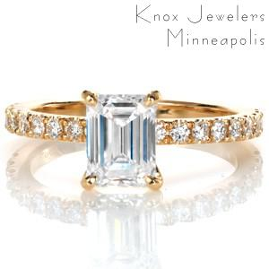 Design 3369 couples a classic four prong center stone setting to an elegant hand carved u-cut diamond band creating a refined look with a timeless appeal. A 1.20 carat emerald cut diamond takes the spotlight in this luscious yellow gold custom engagement ring.