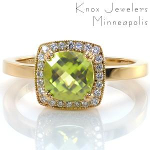 A cushion cut gemstone adds a modern angular outline to a classic halo setting. Design 3370 features a 1.50 carat olive green peridot held in double prongs and framed by twinkling bead set diamonds. A hint of milgrain edging adds texture to this very colorful custom design.