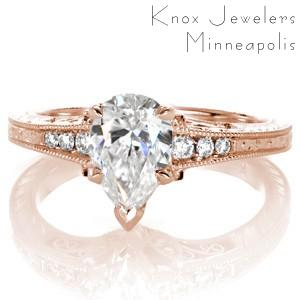 Rose gold custom engagement ring in Sioux Falls with a unique pear cut center diamond held on a band featuring bead set diamonds and hand engraving.