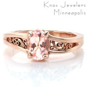 Stunning rose gold and sapphire engagement ring in Tulsa. This gorgeous design features a pale, peachy-pink oval center gem (can me morganite or sapphire)  that is perfectly complimented by the warm hues of the rose gold. The design is completed with hand wrought filigree curls.