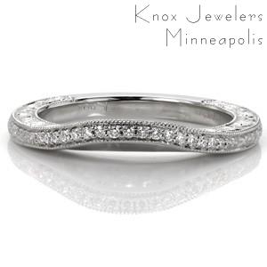 This delicate wedding band was designed to wear against our Design 3248. The band slightly contours to follow the shape of the engagement ring for a perfect fit. Bead set diamonds and floral engraving runs the length of the band top view, with scroll relief engraving and filigree shown on its profile.