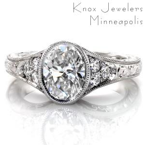 Design 3383 is a custom created engagement ring with antique inspirations. The oval center diamond is captured with a bezel setting that flows into the flared band. Delicate, hand formed filigree curls fill the pockets on the sides of the piece, while intricately carved hand engraving adorns the rest of the design.
