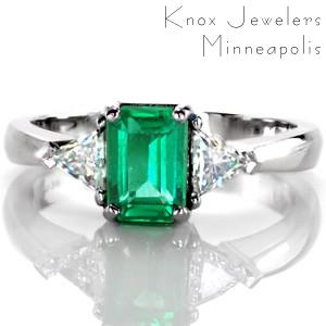 Design 3384 is a beautiful statement piece with a 1.20 carat emerald. The trillion side diamonds compliment the elongated, emerald cut shape of the center stone, while the band tapers in the meet the points of the diamonds. The vibrant, lush green stands out against the cool hues of the metal and diamonds.