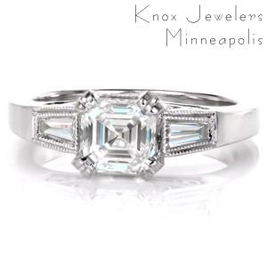 Design 3385 is a stunning blend of geometric shapes and antique inspiration. The long linear facets of the asscher cut is mirrored in the baguette side stones. The band flares to the top of the ring where tapered baguettes are bezel set. Platinum filigree curls adorn the sides of the ring for a vintage appeal.