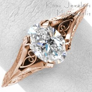 Rose gold engagement ring in Oakland with oval center stone, milgrain texture and scroll filigree.