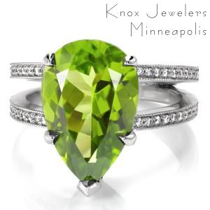 Design 3397 is a contemporary style engagement ring with a bold presence. Crafted in 950 Platinum Ruthenium, the center stone is a vibrant 6.00 carat pear cut natural Peridot gemstone. The split shank is finished with perfectly matched round cut bead set diamonds with milgrain edges.