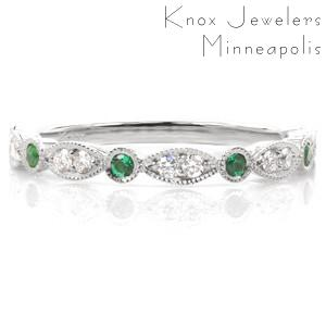 Design 3398 is a colorful take on our popular scalloped wedding band design. This version of the ring features vibrant bezel set round emeralds stationed between bead set diamond marquise shapes. The band is finished with milgrain edging and the profile view features delicate scroll hand engraving.