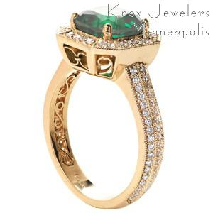 Stunning cushion cut emerald vintage engagement ring in St. Petersburg, Florida. This regal design is shown in yellow gold with a micro pave diamond band and micro pave diamond halo. The basket under the halo, and the inside of the band are both exquisitely detailed with hand formed filigree curls and infinity symbol filigree.