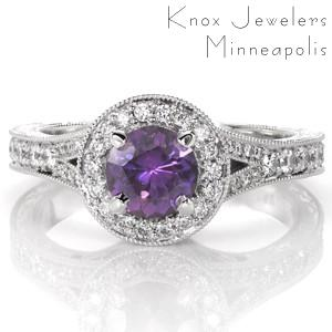 This vintage inspired beauty is adorned with brilliant micro pavé diamonds along the split shank, round halo, and halo apron. The vibrant round purple sapphire is fashioned in a four prong setting in the center of the diamond halo. Milgrain, filigree and scroll engraving enhances its antique charm.