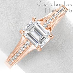 Unique rose gold engagement ring in Fort Worth features a stunning emerald cut center diamond and wide, rose gold and diamond band. The sides are elegantly detailed with intricate filigree curls.