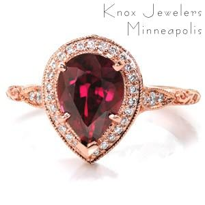 This stunning halo engagement ring is shown in 14 karat rose gold, featuring a 2.30 carat pear cut ruby center stone. The basket under the micro pavé halo features round diamond drapes and a bezel set marquise surprise diamond. The scalloped band is detailed with relief style hand engraving in a scroll pattern.