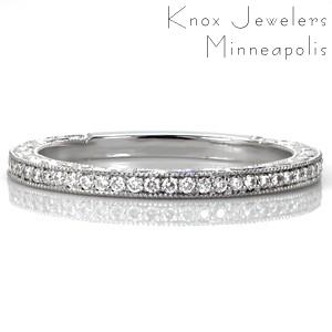 Design 3439 is a step above the traditional diamond wedding band. The top is adorned with brilliant bead-set diamonds and the sides feature unique relief style hand engraving. These intricately hand engraved scroll patterns stand out against the stippled background. Milgrain textured edges create a cohesive final look.