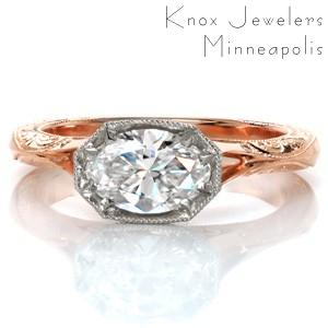 This stunning custom two-toned engagement ring design features a unique, horizontal oval center stone setting. The sides of the faux-bezel center setting are adorned with diamonds to form a horizontal halo. The rose gold split shank band is detailed with hand engraving and filigree curls for a vintage touch.