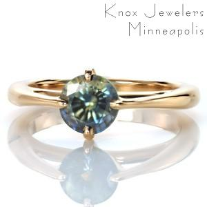 A gorgeous mosaic-like blue-green round sapphire draws the spotlight in this unique custom ring setting. Design 3471 reinterprets a classic engagement ring outline with the addition of an exaggerated profile cathedral and a rotated four prong center setting.