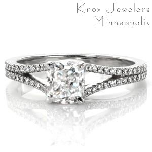 The graceful split shank of the Cushion Bianca creates the perfect contemporary balance of simplicity and style. Set with a 1.00 carat cushion cut center diamond, this four prong setting creates an intricate trellis woven detail. The diamond band gently flares into two rows of diamonds as it reaches the center stone.