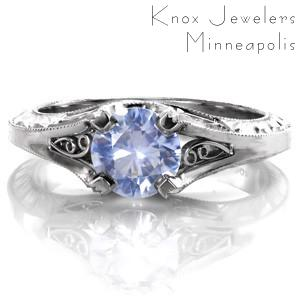 Design 3475 is a stunning vintage inspired custom engagement ring that features an unusual and extraordinary 0.80 carat round light blue sapphire. A four prong setting holds the cornflower blue sapphire with elegant hand formed filigree curls and delicate hand engraving surrounding the center stone.