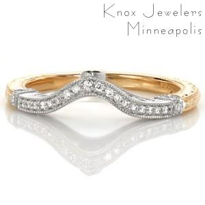This two-tone antique inspired wedding band is simply gorgeous! Carefully crafted filigree curls delicately frame the marquise shaped surprise diamond. micro pavé diamond wraps delineate between the two-tone sections. Intricate hand engraving completes this unique design for a breathtaking look.