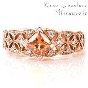 Orange sapphire engagement ring in rose gold in Portland. Rose gold engagement ring featuring a kite-set princess cut sapphire. The antique band style features an openwork starburst pattern set with diamonds.