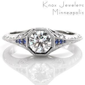 Design 3487 is a stunning, vintage inspired engagement ring featuring a round brilliant center diamond. The knife edge band flares as it approaches the octagonal center setting to reveal bead-set blue sapphires. Hand-formed filigree curls, and elegant hand engraved half-wheat patterns adorn the sides of the band.