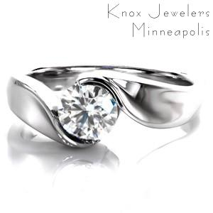 This beautiful Yin-Yang setting features a round brilliant cut diamond as a solitaire. The metal appears to flow up the band like water to wrap around the center stone. The different surfaces are all high polished and the luster of the metal is a perfect compliment to the dazzling sparkle of the diamond.