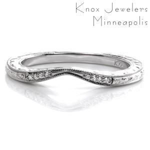 This delicate matching band is created to perfectly fit the curves of the Seville engagement ring. The contour of the wedding band tapers at the middle of the center diamond to minimize the outside curves. Accented with small round diamonds and exquisite hand engraving details, this band is an elegant addition.