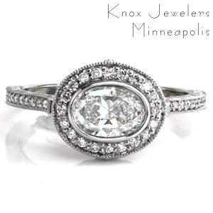 Design 3502 is a stunning halo engagement ring with a damask inspired pattern in the basket. Hand carved, relief style scroll engraving compliments the damask pattern. Micro pavé diamonds are set in the halo and on top of the band. The horizontally set oval center stone is elegantly secured with a bezel setting.