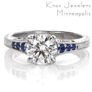 Design 3503 captures the rich cobalt blues within its round graduating sapphires. Vintage-inspired details of milgain, filigree, and hand engraving adorn the sides of the band. A 1.20 carat round brilliant center stone is fashioned within the 14k White Gold setting for added radiance and shine.