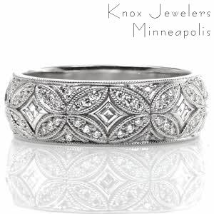 Design 3516 conveys elegance with its curving lines and intricate interlocking pattern. This wide, half-round band features bezel set carre cut diamonds surrounded by mosaic-like sections of bead set side diamonds. Milgrain edging adds the final vintage inspired touch to this exquisite custom ring.