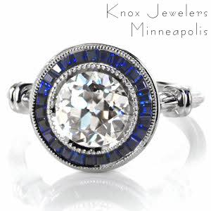 Custom Design 3518 is truly a show-stopper with its dazzling 2.00 carat round center diamond and deep blue sapphire tapering banquette framing halo. This vintage inspired custom ring features milgrain edging, wrapped shoulders, and a pierced under basket.